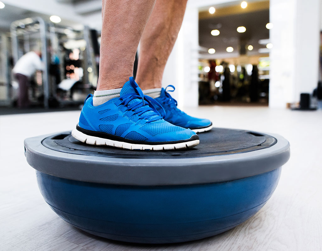 Man balancing on bosu ball
