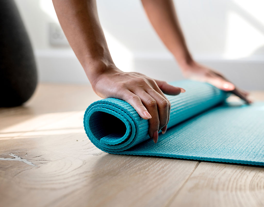 Lady rolling up a pilates mat