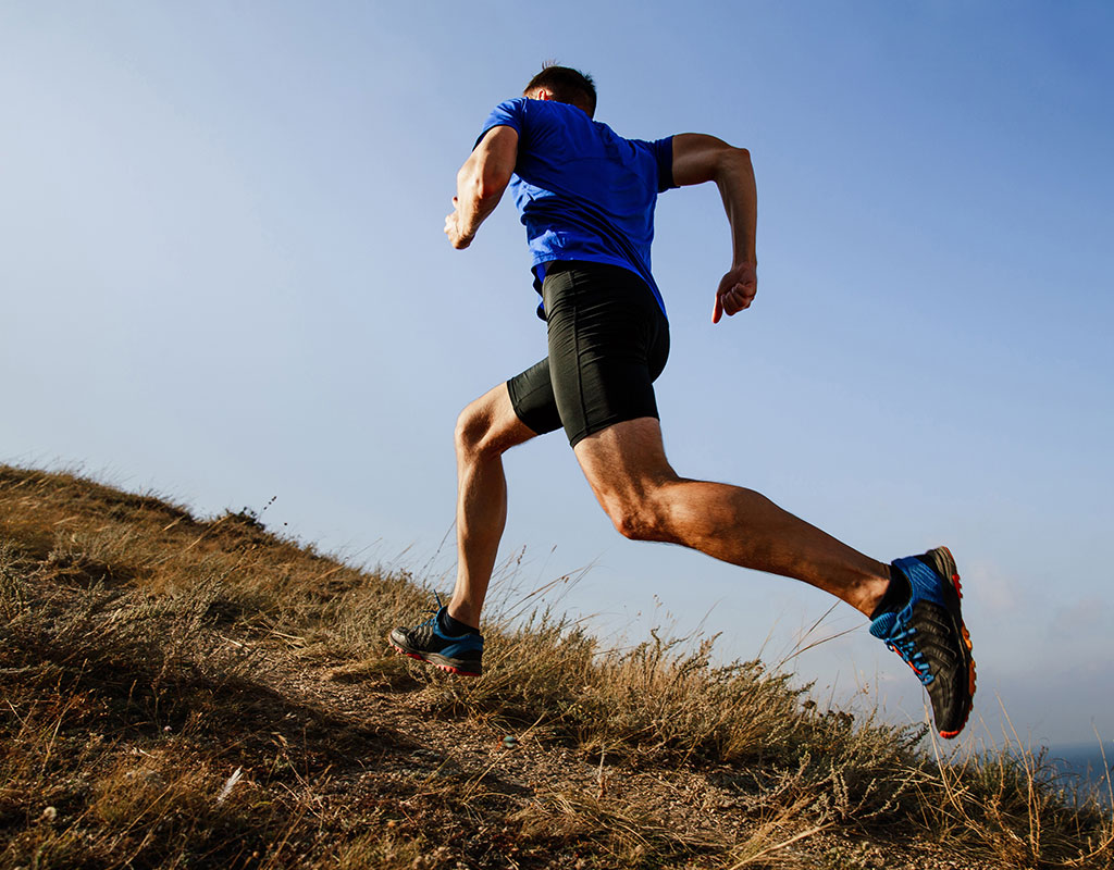 Athletic man running up a hill