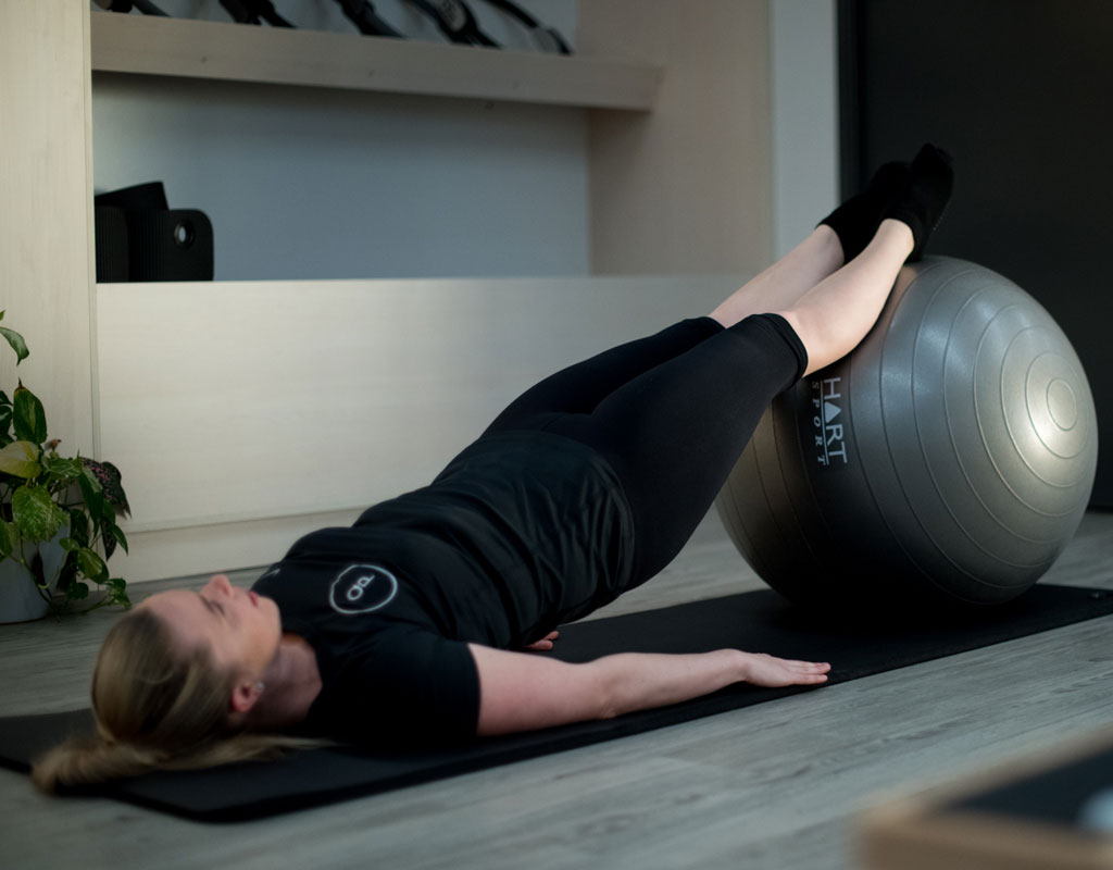 Woman from Q Pilates exercising on mat with gym ball